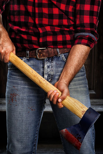 Midsection of lumberjack holding axe outdoors
