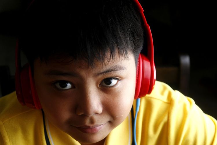 Close-up of boy listening to headphones