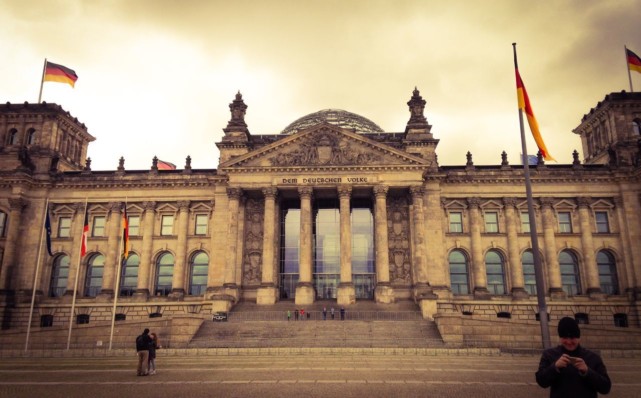 People Outside Reichstag Against Cloudy Sky