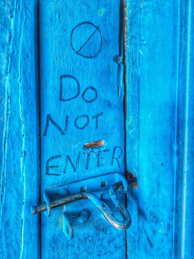 Close-up of text on blue door