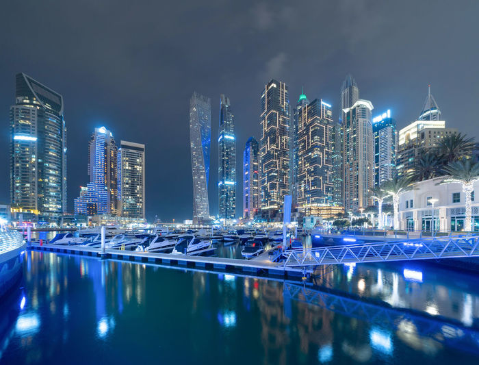 Illuminated buildings by swimming pool at night