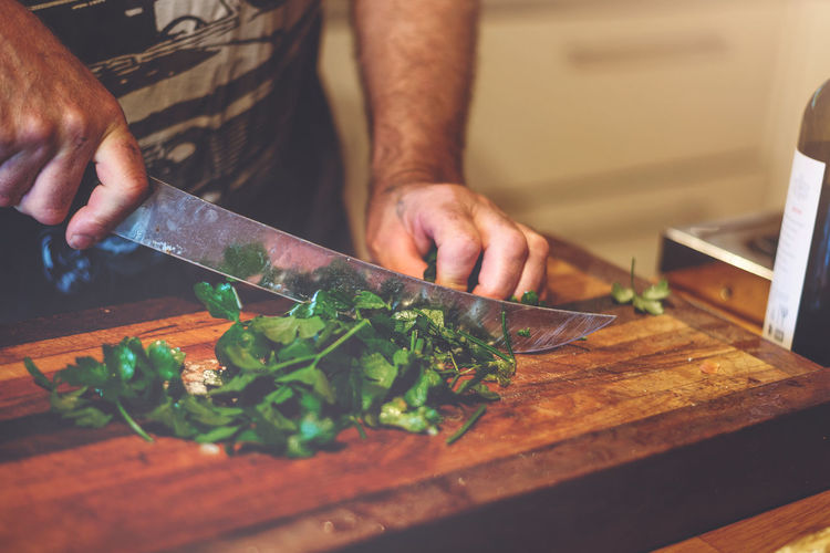 Midsection of man cutting vegetables on cutting board in kitchen