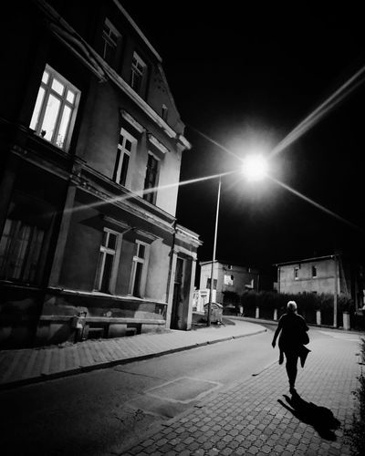 Rear view of man walking on illuminated street amidst buildings in city