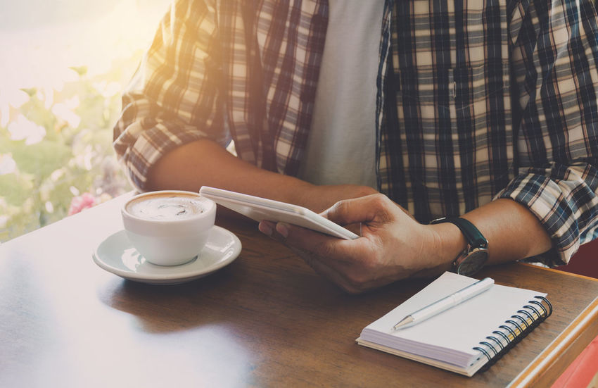 Male using a smart phone with coffee cup on wooden table. Coffee Table Cup One Person Coffee - Drink Mug Drink Coffee Cup Wireless Technology Technology Food And Drink Refreshment Holding Real People Mobile Phone Connection Midsection Telephone Lifestyles Communication Saucer Crockery Hand Outdoors
