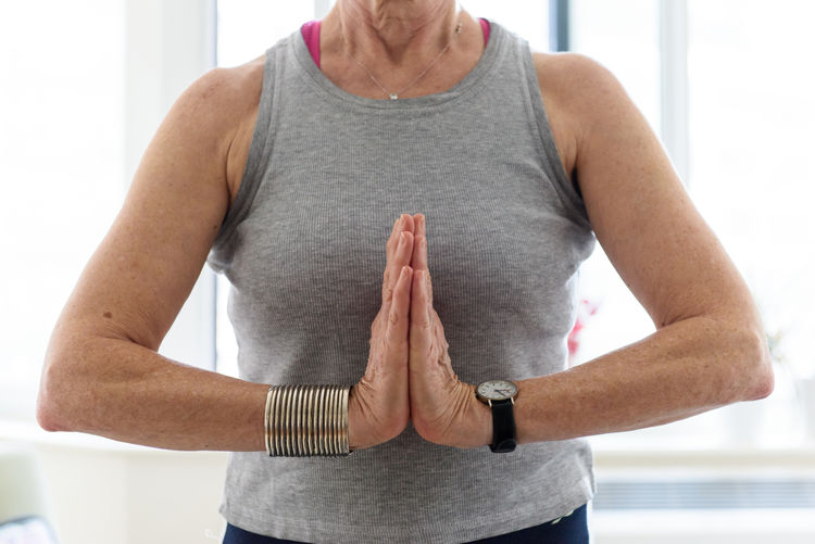 Midsection of woman with arms raised standing at home