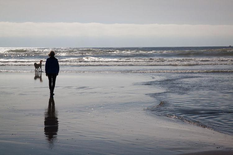 Woman walking on calm beach against sky