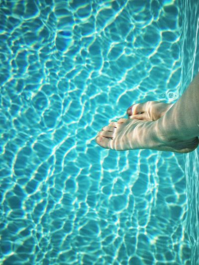 Low section of person sitting in swimming pool