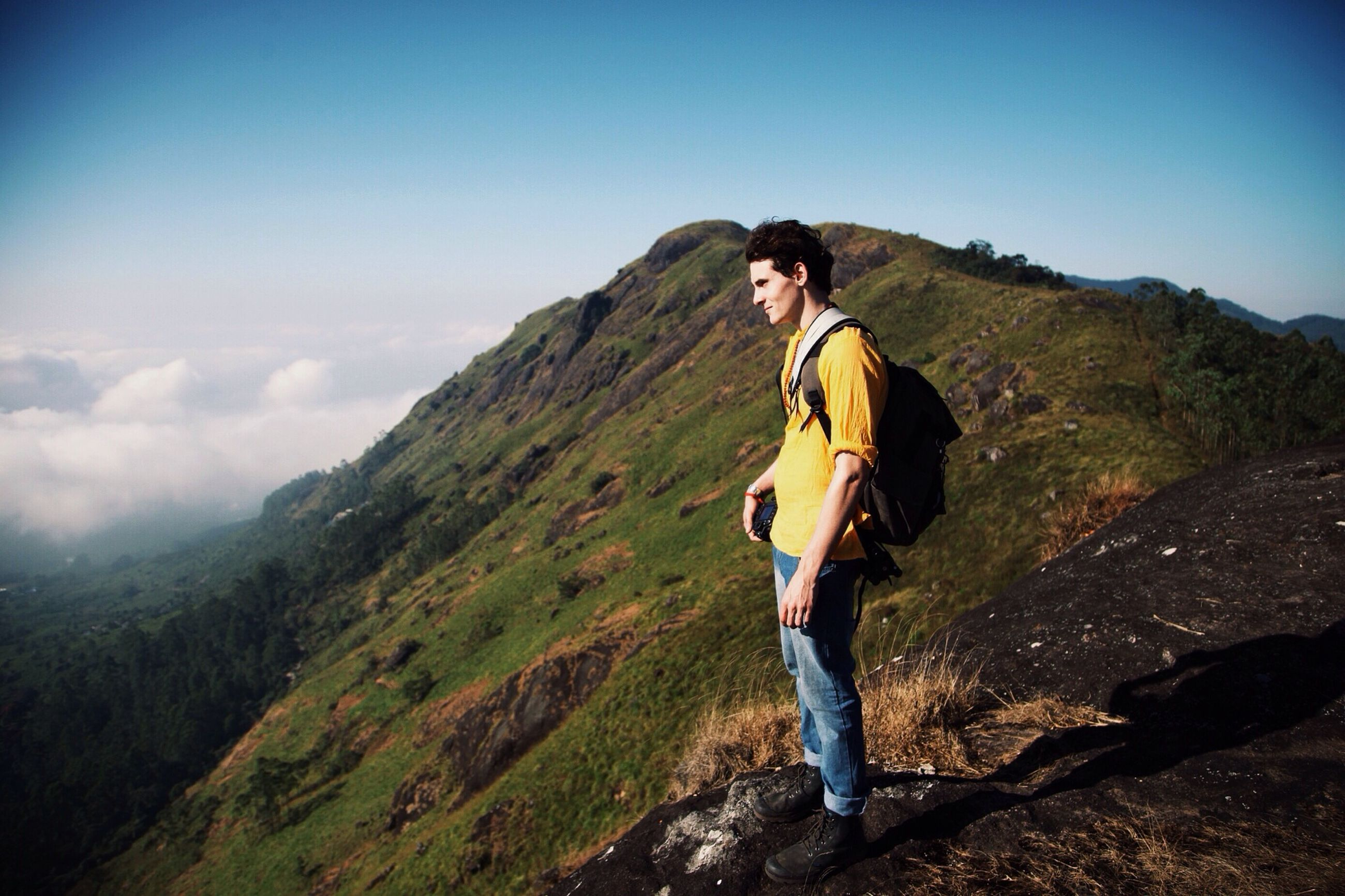 young adult, casual clothing, lifestyles, mountain, full length, leisure activity, standing, person, young women, sky, portrait, front view, looking at camera, mountain range, landscape, tranquility, tranquil scene