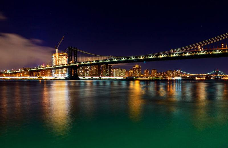 Illuminated manhattan bridge over river at night