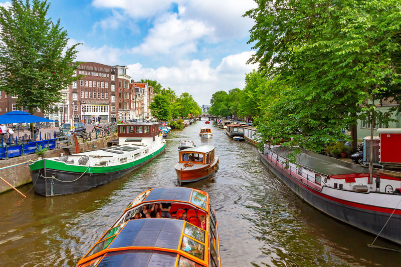 Boats in idyllic Amsterdam Amsterdam Netherlands Canal Gracht City Travel Tourism Water Green Destination Vacations Spring Summer Bridge Architecture Nature Nature Traveling Sightseeing Dutch Holland Romantic Transportation Tourist Leisure Activity