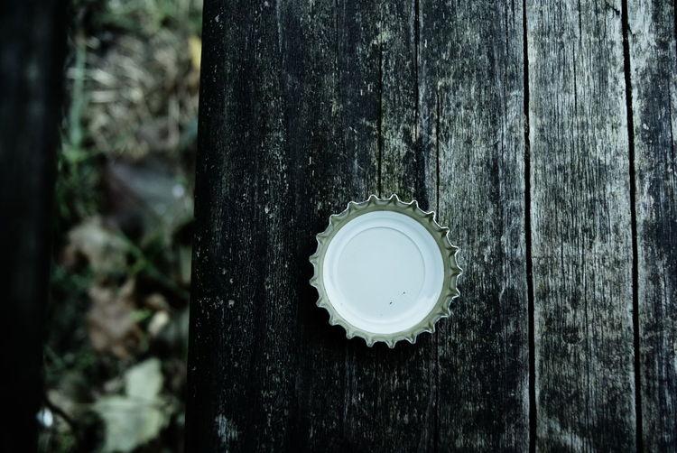 Close-up of metallic bottle cap on wood