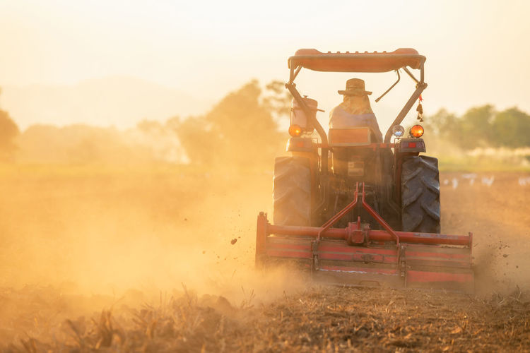 Man working on agricultural field during sunset