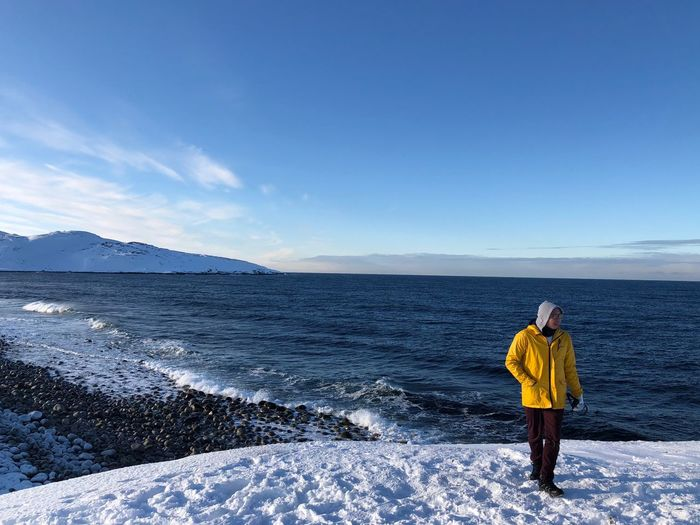 Man Standing On Snowcapped Mountain With Sea In Background