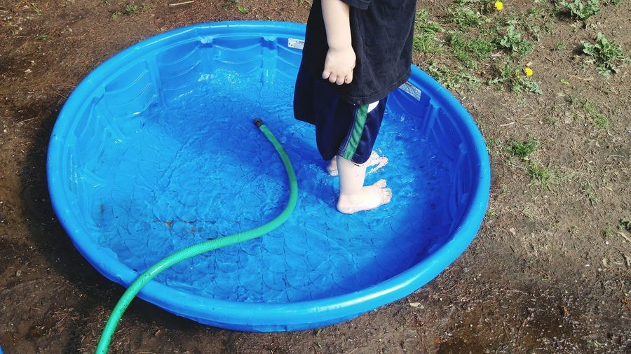 Low Section Of Boy Standing In Wading Pool