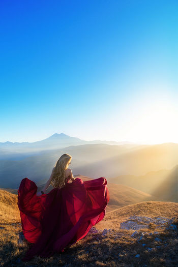 Rear view of woman wearing red dress on mountain against clear blue sky during sunset
