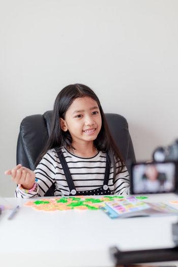 Smiling girl blogging at home