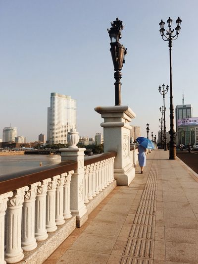 Rear view of woman walking by railing in city against clear sky