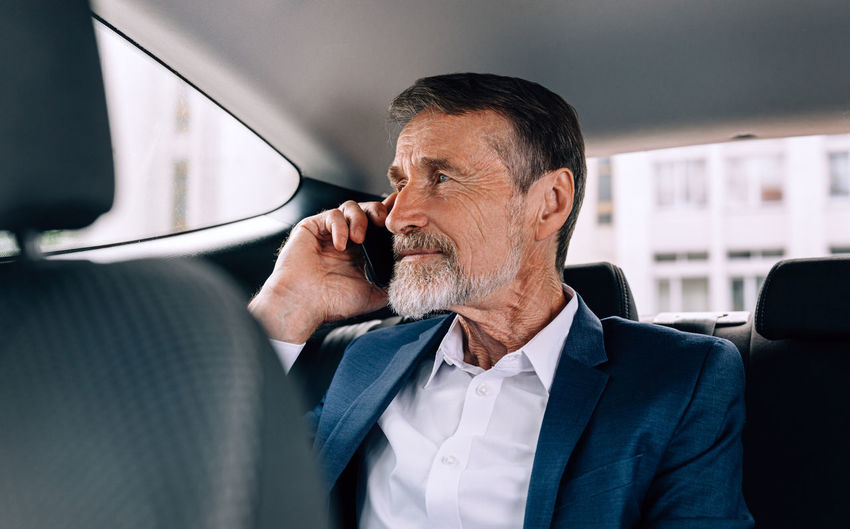 Businessman talking over mobile phone in car