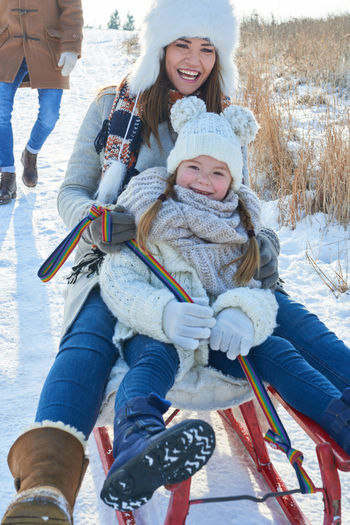 Man standing against mother and daughter sledding on snow covered field