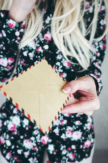 Midsection of woman holding envelopes
