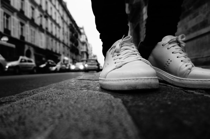 Low section of person wearing shoes on street