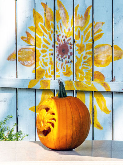 Carved pumpkin sits in front of a pretty flower graphic painted on an outdoor fence