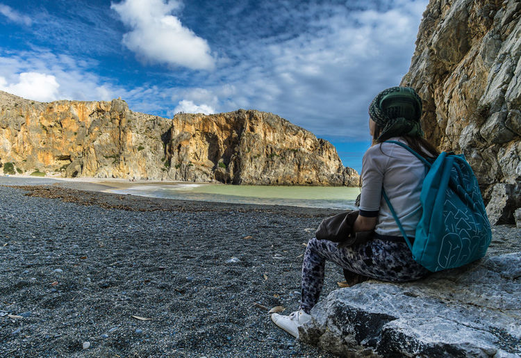 Rear view of woman sitting on rock by sea against sky