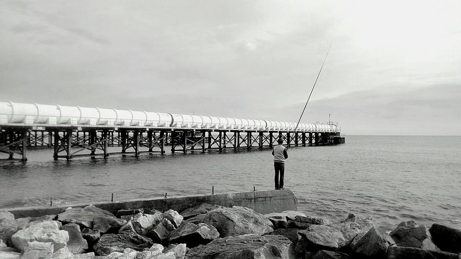 Rear view of man standing on shore and fishing