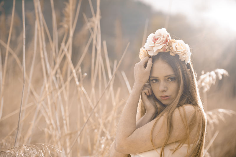 Beautiful young women with a headpiece in the nature Young Adult Plant One Person Beauty Women Beautiful Woman Young Women Adult Nature Hair Long Hair Hairstyle Outdoors Contemplation Headpiece Flowers Field Warm Daylight People Moody Attractive Cute Model Nature