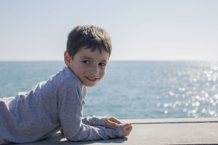 Smiling boy looking away while lying on retaining wall against sea and sky