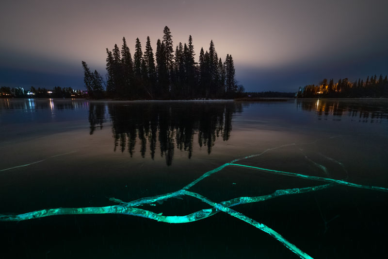 Ness Lake froze perfectly this year without wind or snow, turning it into one large transparent ice rink for a few amazing days of skating. The ice was clear enough to see submersed logs and schools of fish below your feet as you skated. This shot is looking east towards the island and I used a high intensity led flashlight to light up some of the foreground cracks in the ice. The fractured ice reflects the light down the cracks much in the same way light travels down optic fiber. Any light which escapes the primary fracture travels away sideways though the ice without being visible to the observer above unless picked up by another crack and reflected upwards. Reflection Lake Water Sky Beauty In Nature Tranquility Tranquil Scene Nature Scenics - Nature No People Idyllic Non-urban Scene Outdoors Illuminated Waterfront Reflection Lake Frozen Lake Ice Ice Cracks Ice Fractures Night Photography Ness Lake, Northern British Columbia, Canada Frozen Trees Island