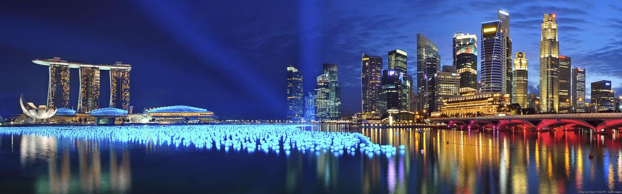 Marina bay sands by bay of water in illuminated city at night