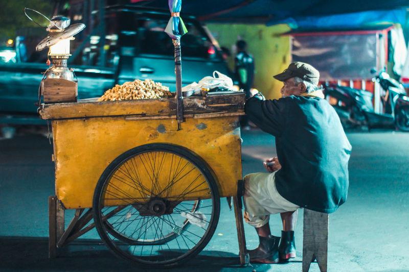 Full length of vendor sitting by cart