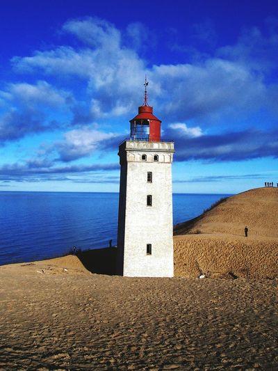 Lighthouse by sea against cloudy blue sky on sunny day