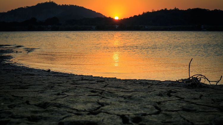 lingering light of the setting sun River Setting Sun Sunset Nature Beauty In Nature Scenics Sun Tranquility Orange Color No People Outdoors Day Mountain Water