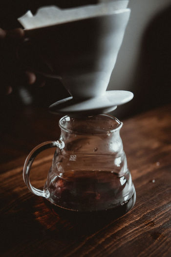 Cropped image of hand holding cup over black tea in glass jar