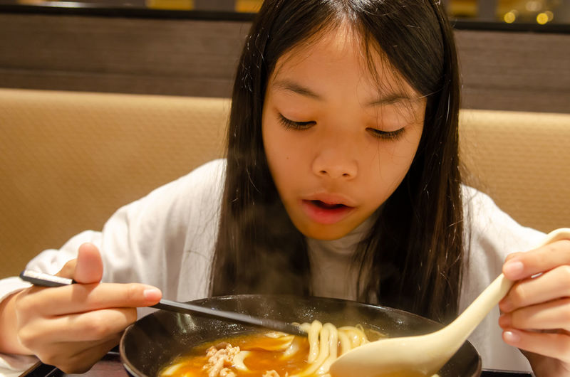 Close-up of girl eating noodles with chopsticks at restaurant