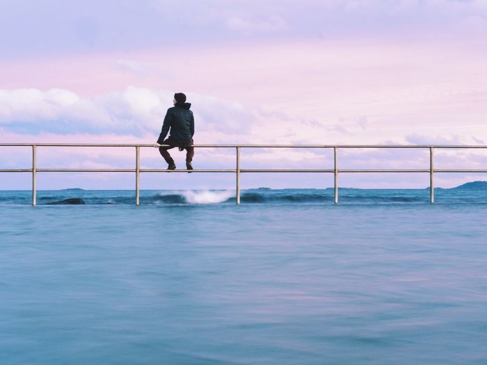 Rear view of man sitting on railing amidst sea