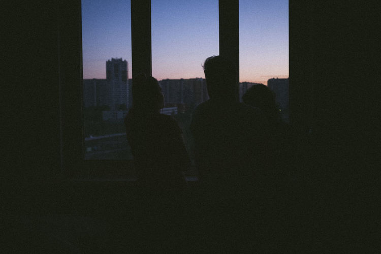 Silhouette people standing in city against sky seen through window