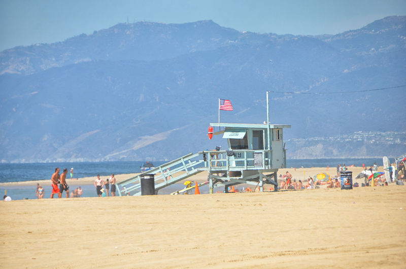 Land Water Beach Group Of People Sea Sky Mountain Nature Sand Day Real People Lifeguard Hut Men Man Made Structure Holiday Crowd Hut Built Structure Outdoors Beach Hut California Stars And Stripes Star Spangled Banner Venice Beach