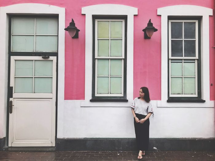 Full length of woman standing against house
