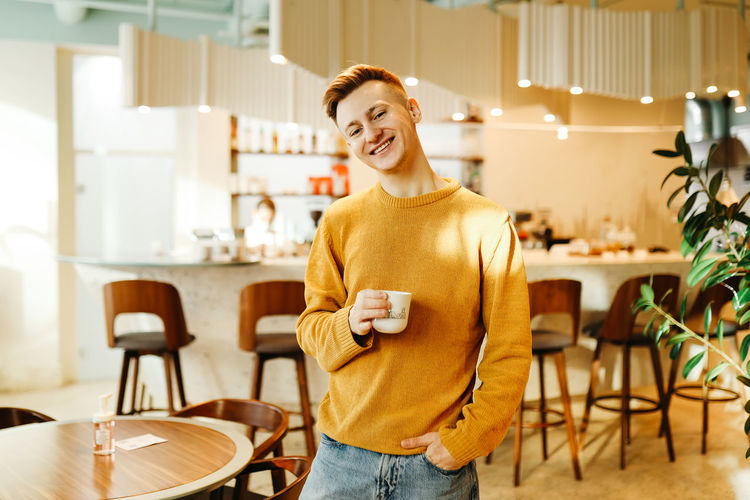 Portrait of smiling young man standing on chair
