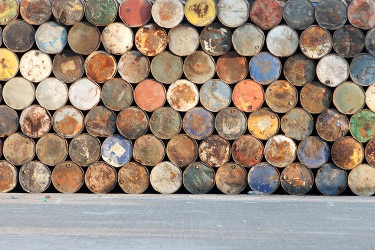 Stack Of Rusty Metallic Barrels On Footpath