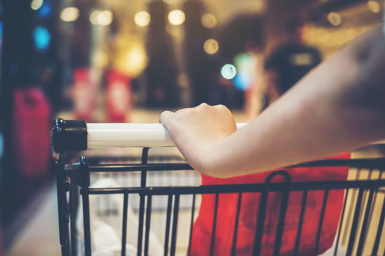 Cropped hand of woman holding push cart at supermarket