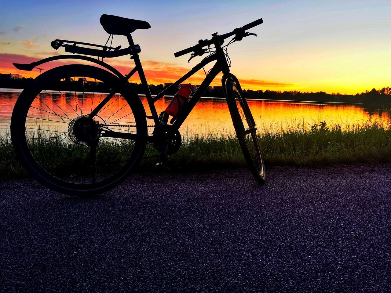 BICYCLE PARKED ON ROAD AGAINST SKY DURING SUNSET
