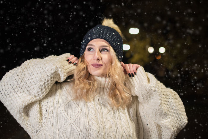 young woman happy on snowy night Cheerful Cold Temperature Happiness Knit Hat Knitted  Only Women Outdoors Portrait Smiling Snow Snowing Sweater Warm Clothing Winter