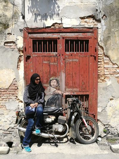 Full length of woman sitting on motorcycle against building