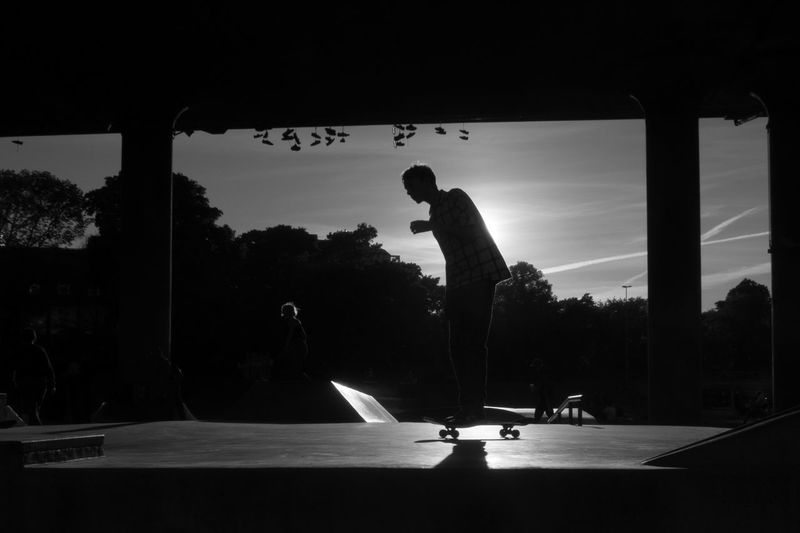 Silhouette man playing soccer against sky