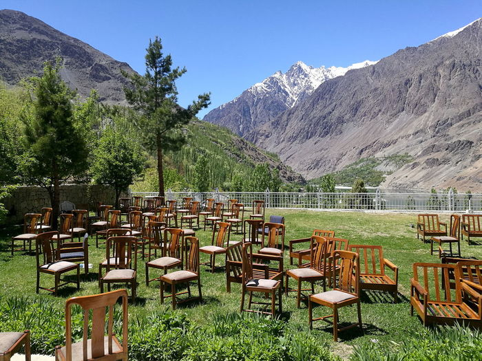 Empty chairs and tables on field by mountains against sky