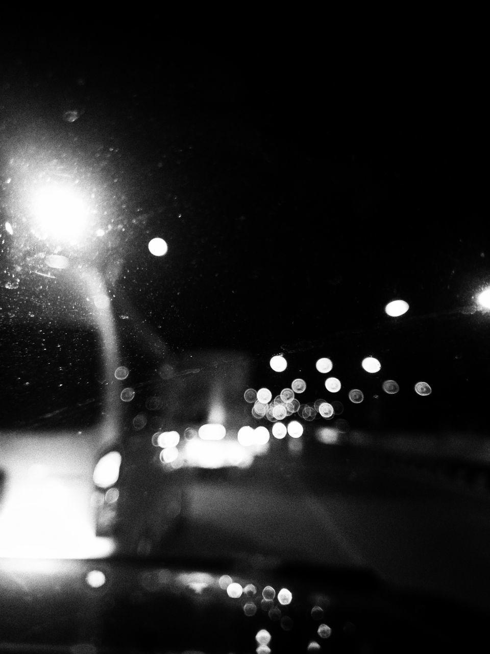 DEFOCUSED IMAGE OF ILLUMINATED LIGHTS ON WET WINDSHIELD